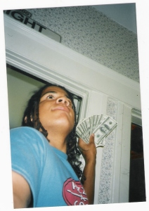 This is a picture of beckett haight as a high school student holding up a ton of 100 dollar bills, has braided hair and it could be the world's first selfie