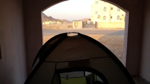 This is a picture of a tent in a bus station in oman and it is looking out into the light of the day
