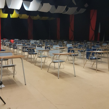 Picture of a gym with a lot of desks lined up for finals testing